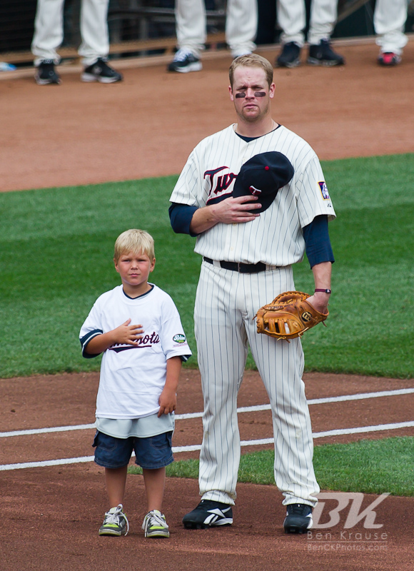 Minnesota Twins 1st baseman Justin Morneau stands with a young fan during the national anthem before a game against the Detroit Tigers on August 28, 2011 at Target Field in Minneapolis, Minnesota.  The Twins defeated the Tigers 11 to 4.