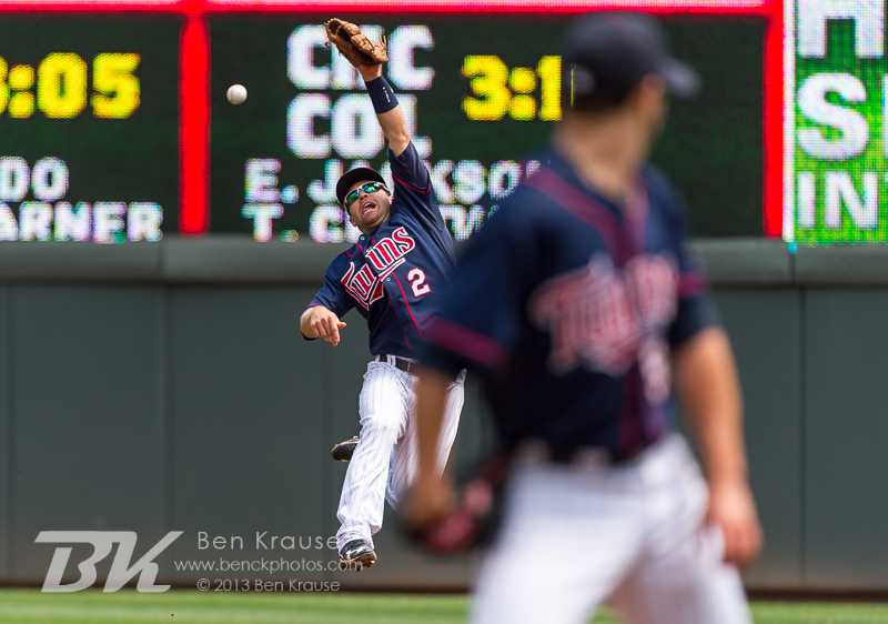 Brian Dozier #2 of the Minnesota Twins attempts to make a leaping catch as Scott Diamond #58 watches from the mound during a game against the Cleveland Indians on July 21, 2013 at Target Field in Minneapolis, Minnesota.  The Indians defeated the Twins 7 to 1.  Photo by Ben Krause
