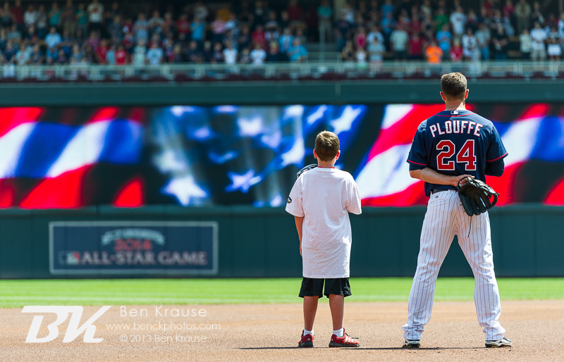 Trevor Plouffe #24 of the Minnesota Twins stands with a young fan during the national anthem before a game against the Cleveland Indians on July 21, 2013 at Target Field in Minneapolis, Minnesota.  The Indians defeated the Twins 7 to 1.  Photo by Ben Krause
